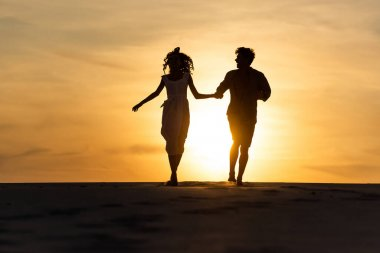 Silhouettes of man and woman running on beach against sun during sunset stock vector