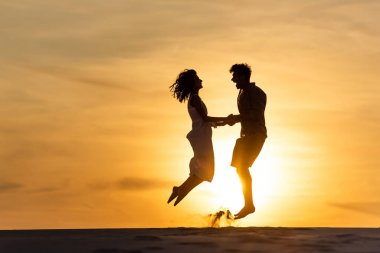 Side view of silhouettes of man and woman jumping on beach against sun during sunset stock vector