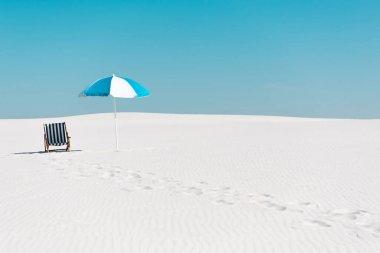 Güverte sandalyesi ve şemsiyesi kumlu sahilde açık mavi gökyüzünde