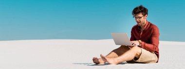 Genç serbest çalışan kumlu sahilde açık mavi gökyüzüne karşı dizüstü bilgisayar kullanıyor, panoramik çekim