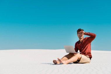 Kumsalda mutlu bir serbest yazar, açık mavi gökyüzüne karşı dizüstü bilgisayar kullanıyor.