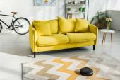 selektivní zaměření robotického vysavače prací koberec v blízkosti pohovky v moderním obývacím pokoji