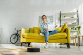 Photo attractive woman using laptop while robotic vacuum cleaner washing carpet in living room