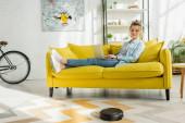 glückliche Frau mit Laptop, während Staubsaugerroboter Teppich im Wohnzimmer waschen