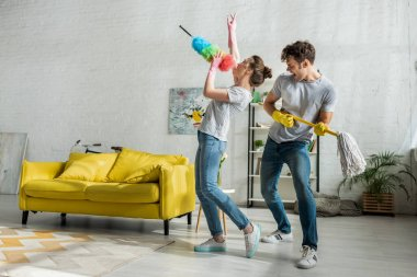 man and woman with household singing while doing spring cleaning in living room