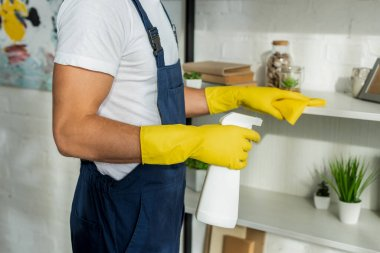 cropped view of cleaner in overalls cleaning rack shelves in apartment