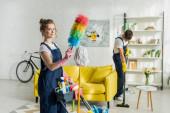 selektivní zaměření mladého a šťastného čističe držícího prachový kartáč v blízkosti čisticího vozíku