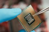 Fotografie Nahaufnahme von Computer-Mikrochip und Pinzette in den Händen des Ingenieurs