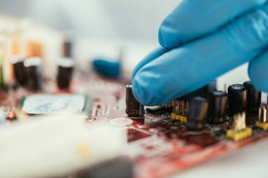 Selective focus of hand of engineer in rubber glove near computer motherboard stock vector