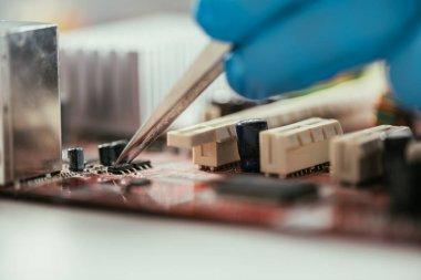 Cropped view of engineer testing computer motherboard with tweezers stock vector