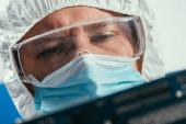inženýr v ochranných brýlích a lékařské masce s počítačovou komponentou