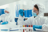 Photo biochemist holding test tube with blood sample near colleague in laboratory