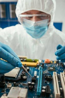 Selective focus of engineer holding tweezers while testing computer motherboard stock vector