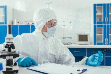 biochemist in hazmat suit sitting near microscope and clipboard in laboratory