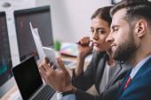 Az irodai számítógépek közelében dolgozó, okostelefont használó információbiztonsági elemzők szelektív fókusza
