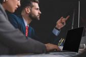 Selektivní zaměření analytiků bezpečnosti informací pracujících s notebooky a počítači u stolu izolovaného na černém