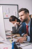 Selektivní zaměření datových analytiků pracujících s papíry a digitálními zařízeními u stolu v kanceláři
