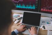 Selektiver Fokus des Datenanalysten mittels Laptop in der Nähe von Diagrammen auf Papieren und Computermonitoren auf dem Tisch