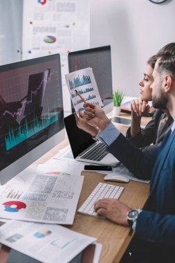 Side view of data analysts working with charts on paper and computer monitors at table stock vector