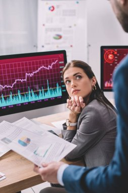 Selective focus of data analyst looking at colleague holding papers with graphs in office stock vector