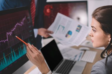 Selective focus of information security analyst pointing on charts on computer monitor near colleague with papers isolated on grey stock vector