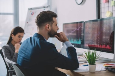 Selective focus of analysts planning security software for computer systems at table in office