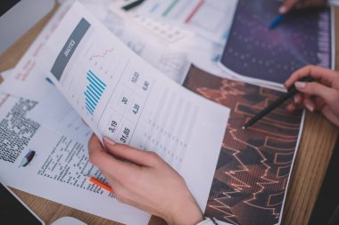Selective focus of analysts using papers with graphs while working at table stock vector