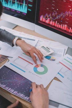 Cropped view of data analysts using charts near calculator and computer monitors on table stock vector