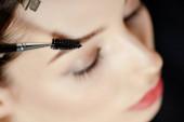 selektivní zaměření štětce obočí u ženy se zavřenýma očima