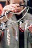 selektivní zaměření stylistky dotýkající se perlového náhrdelníku v blízkosti náušnic