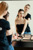 Fotografie selective focus of make up artist near model and decorative cosmetics