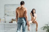 Mann vor heißem Mädchen auf Küchenschrank sitzend und lächelnd