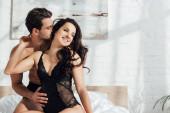 Fotografie Mann umarmt und küsst hübsche und glückliche Frau auf Bett im Schlafzimmer