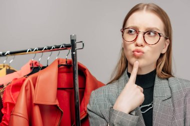 Pensive stylist in glasses touching face while thinking near trendy clothing isolated on grey stock vector
