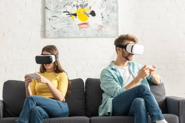 Young couple in vr headsets using smartphones on couch stock vector