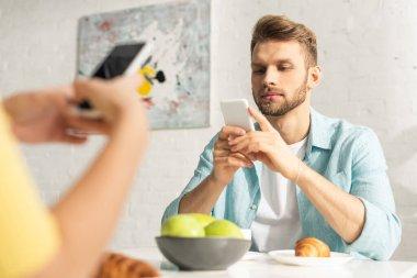 Selective focus of man using smartphone near girlfriend during breakfast in kitchen stock vector
