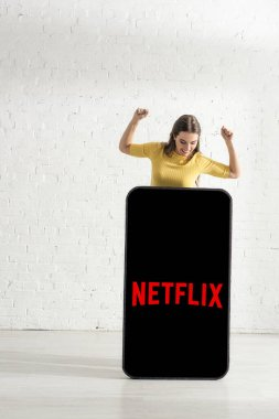 KYIV, UKRAINE - FEBRUARY 21, 2020: Smiling girl showing yes gesture and looking at model of smartphone with netflix app stock vector