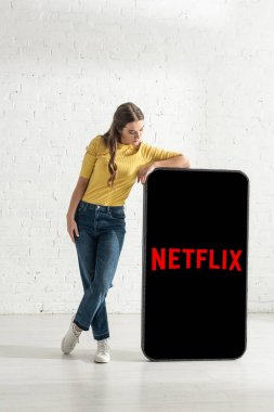 KYIV, UKRAINE - FEBRUARY 21, 2020: Attractive young woman standing near model of smartphone with netflix app stock vector