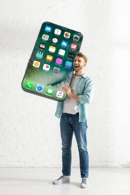 KYIV, UKRAINE - FEBRUARY 21, 2020: Happy man holding big model of smartphone with iphone screen stock vector
