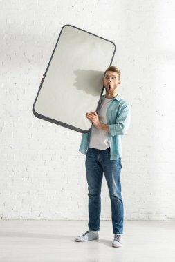Shocked man holding model of smartphone near white brick wall stock vector