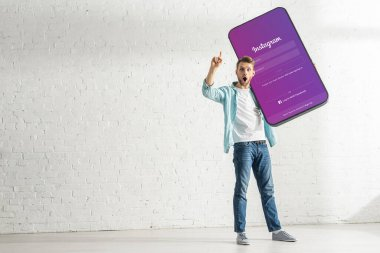 KYIV, UKRAINE - FEBRUARY 21, 2020: Excited man showing solution gesture while holding model of smartphone with instagram app stock vector