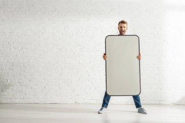 Cheerful man holding big model of smartphone near white brick wall stock vector