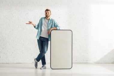 Smiling man showing shrug gesture near big model of smartphone stock vector