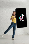 KYIV, UKRAINE - FEBRUARY 21, 2020: Beautiful young woman pointing with finger at big model of smartphone with TikTok app at home