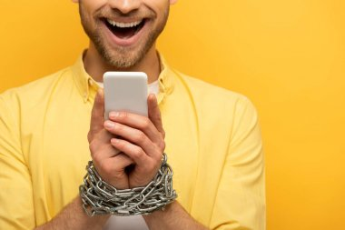 Cropped view of happy man with chain around hands holding smartphone on yellow background stock vector