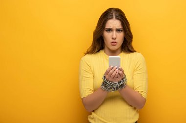 Confused woman with metal chain around hands holding smartphone and looking at camera on yellow background stock vector