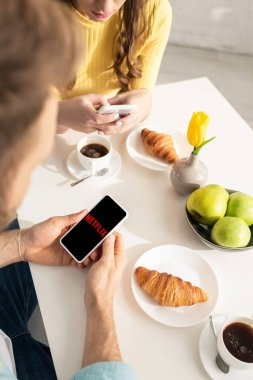KYIV, UKRAINE - FEBRUARY 21, 2020: Selective focus of man holding smartphone with netflix app near breakfast in kitchen stock vector