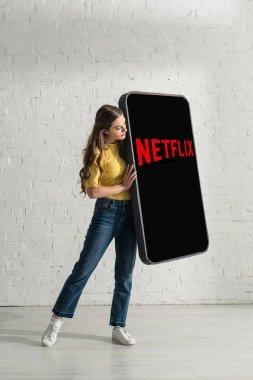 KYIV, UKRAINE - FEBRUARY 21, 2020: Beautiful woman holding huge model of smartphone with netflix app near white brick wall stock vector