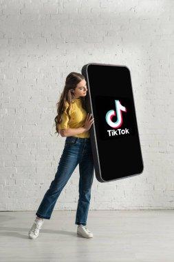 KYIV, UKRAINE - FEBRUARY 21, 2020: Beautiful young woman holding big model of smartphone with TikTok app near white brick wall stock vector