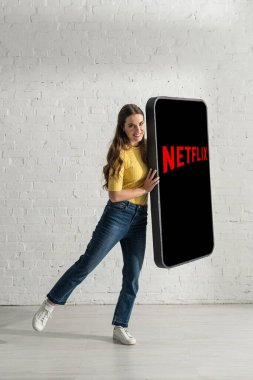 KYIV, UKRAINE - FEBRUARY 21, 2020: Attractive girl smiling at camera while holding big model of smartphone with netflix app stock vector
